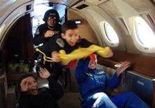 In this photo released by Ecuador's Civil Space Aviation Agency, Jules Nader, 7, center, floats with his brother Gerard Nader, 10, bottom left, and friend Julia Velastegui, 17, behind right, during a zero-gravity flight in an air force plane in Guayaquil, Ecuador, Thursday, June 19, 2008.