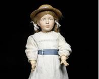 The World's Most Expensive Doll sold at auction wears a white dress with lace sleeves and a powder blue ribbon sash which matches her finely painted blue-grey eyes. A delicate straw hat sits on top of her auburn, plaited hair. This doll has unique pierced ears and a more adult expression than the other dolls, capturing a striking portrait of a young lady. No other example of this doll is known. It is therefore possible that she was an experimental mold.