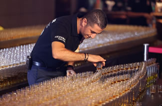 Ahmad Taher, food and beverage manager for Citymax Hotels in Dubai, United Arab Emirates, fixes a shot glass before attempting the world's longest domino drop shot. The Huddle Sports Bar & Grill successfully 'dropped' 4,578 glasses of Camros whiskey into Bazooka energy drink.