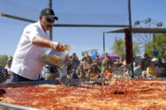 Robert V. Estrada sprinkles cheese over the world s largest flat enchilada Sunday during the 33rd The Whole Enchilada Fiesta in Las Cruces. The making of the giant enchilada returned to the fiesta this year. Last year, the equipment used to make it wasn t ready in time for the state gas commission inspection.