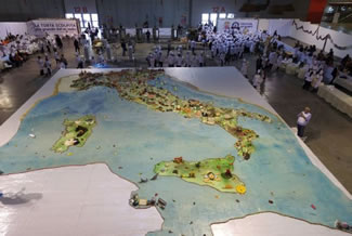 A giant cake baked in Italy that measures over 16 metres long and weighs more than 1,000 kg has set the world record for the world's largest cake sculpture. The cake, measuring 16.46 metres long by 13.94 metres wide, was decorated with a map of Italy and its most famous landmarks, including the Leaning Tower of Pisa and the Alps. The cake had a total surface area of 244 square metres and weighed more than a tonne (1,000 kg).