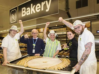Asda Barnstaple store manager Andy Felix and bakery manager Nicole O'Connor with members of the bakery team and the gigantic 31 inch Easter biscuit.