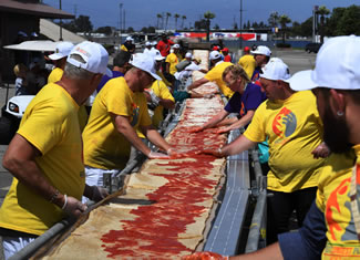 Volunteers at the Auto Club Speedway in Fontana, California, made the longest pizza with a length of 1.32 miles (2.13 kilometers). Approximately 17,700 lbs. of dough, 5,000 lbs. of tomato sauce and 3,900 lbs. of mozzarella cheese were used to create the longest pizza.