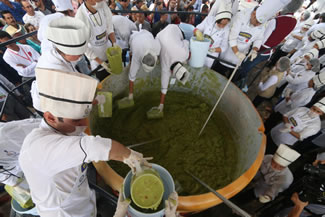 Volunteers from a culinary school mix mashed avocados as they attempt to set a new World Record for the largest serving of guacamole in Concepcion de Buenos Aires, Jalisco, Mexico.