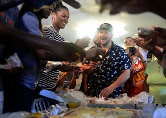 Crown Pizza owner Taso Vitsas, center, looks at Connecticut Sun player Alyssa Thomas as she helps put cheese on a pizza during an attempt to break the world record for most types of cheese on a pizza.