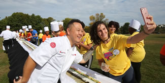 Purchase College students and staff break a record for the world's longest California roll overseen by Food Network's celebrity chef Jet Tila Oct. 11, 2017 in Purchase. The mega maki required approximately 500 cups of vinegared rice, 800 sheets of nori paper, 125 avocados and 200 pounds of surimi, a fish paste.