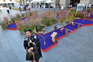: Bagpiper Charles Rutan of Philadelphia plays the pipes next to a miniature golf course set up as part of