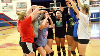 THE LADY PATRIOT volleyball team gathers for a brief celebration huddle after setting a new world record for most consecutive volleyball passes.