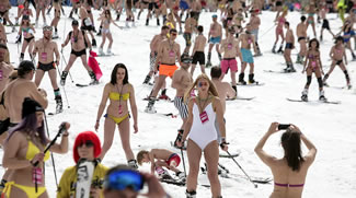 Skiers and snow boarders descend from a slope as they attempt to break the record for mass skiing in swimming suits at Rosa Khutor resort near Sochi, Russia.