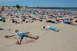 The Ludington Daily News and The Muskegon Chronicle report 1,387 people angelically assembled on a Lake Michigan beachfront in Ludington on Saturday and worked their magic for 30 seconds. That far surpasses the roughly 350 who made sand angels for 15 seconds two years ago in Pembrokeshire, Wales.