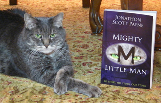 Little Man, crossing his paws in a characteristic pose, tolerates having his photo made with the book his owner, Madison, Ala., engineer Jonathon Scott Payne, has written about their lives together.