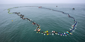 511 surfers joined hands today just off the pier in Huntington Beach, setting a World Record for the largest paddle out.