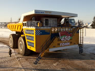 The truck BelAZ-75710 is over 20 meters long, almost ten meters wide, and around eight meters tall. It has a turning radius of approximately 20 meters and a top speed of 64 km/h. Its all-wheel drive and four-wheel hydraulic steering ensure that the tires, which are around four meters tall, don't get stuck in rough terrain.